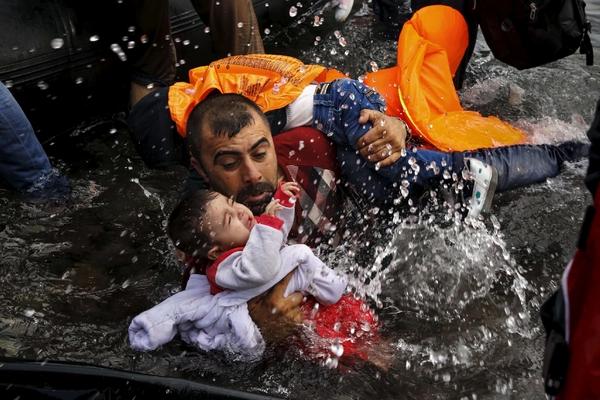 Nelle braccia del padre: sopravvissuti a un naufragio davanti a Lesbo il 24 settembre 2015 (Foto Lapresse/Reuters)